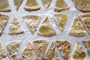 brushing oil and salt onto pita bread for 2 ingredient pita chips
