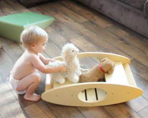 son playing with STEM toy wooden rocker 1