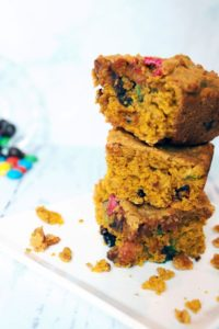 stacked trail mix cookies bars with candy in background 1