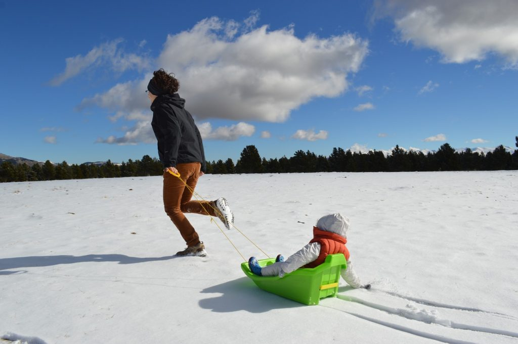 toddler sledding with mom