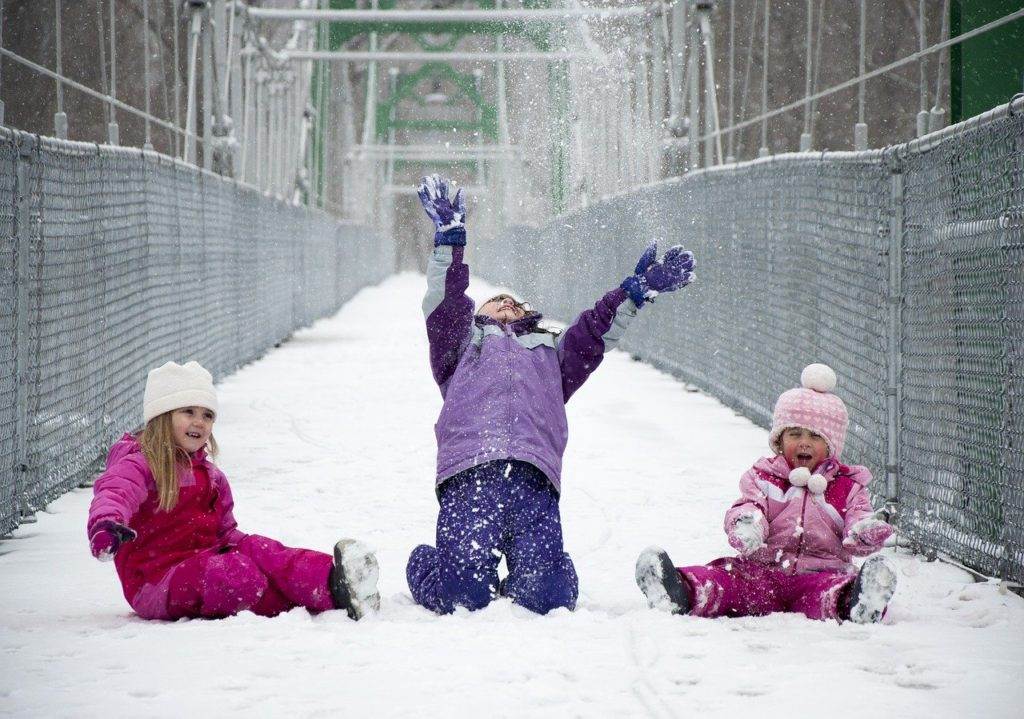 girls playing outside in the cold snow