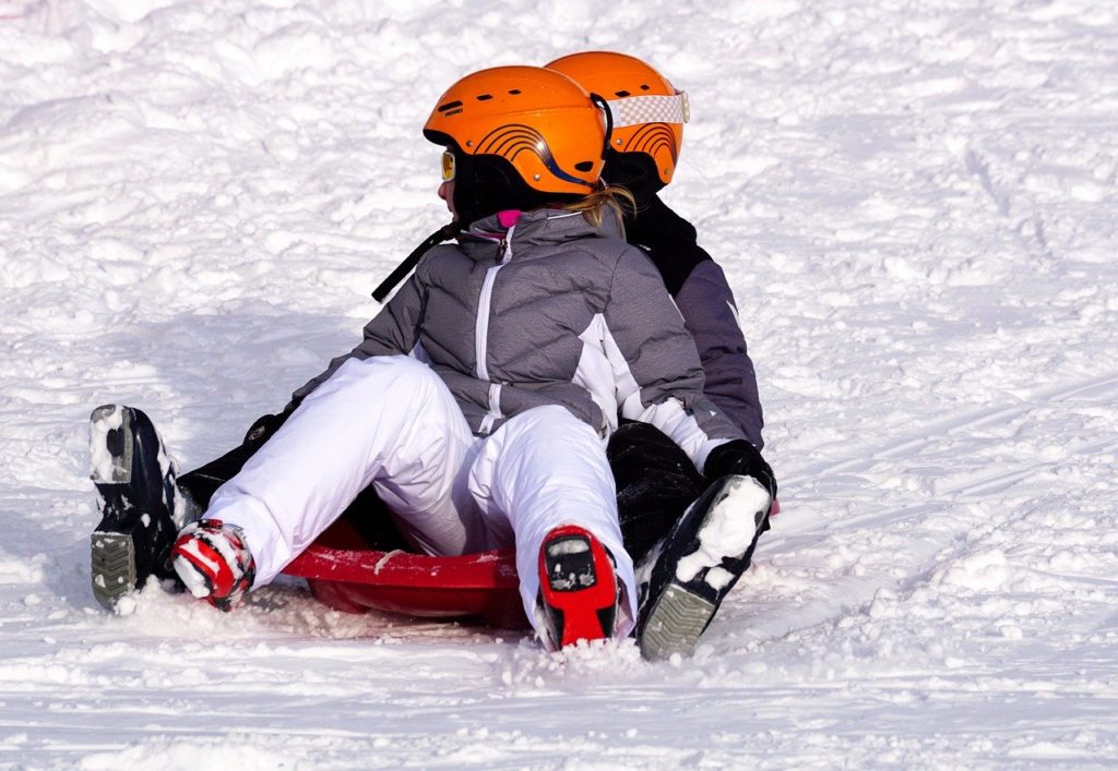 kids play on winter sleds in the cold snow