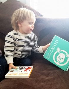 toddler grinning at bookroo box of books