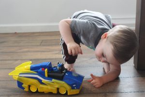 toddler squatting to play with toy-min