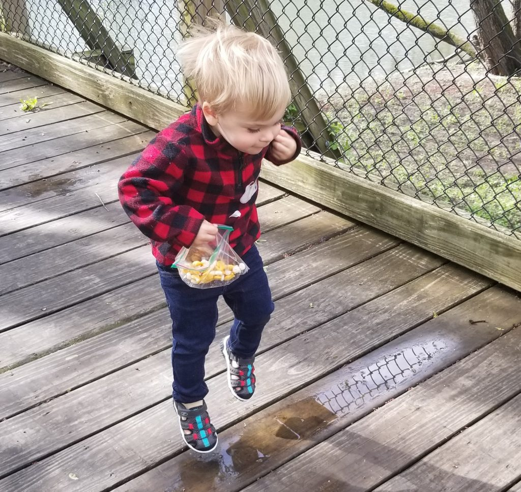 toddler jumping in puddle