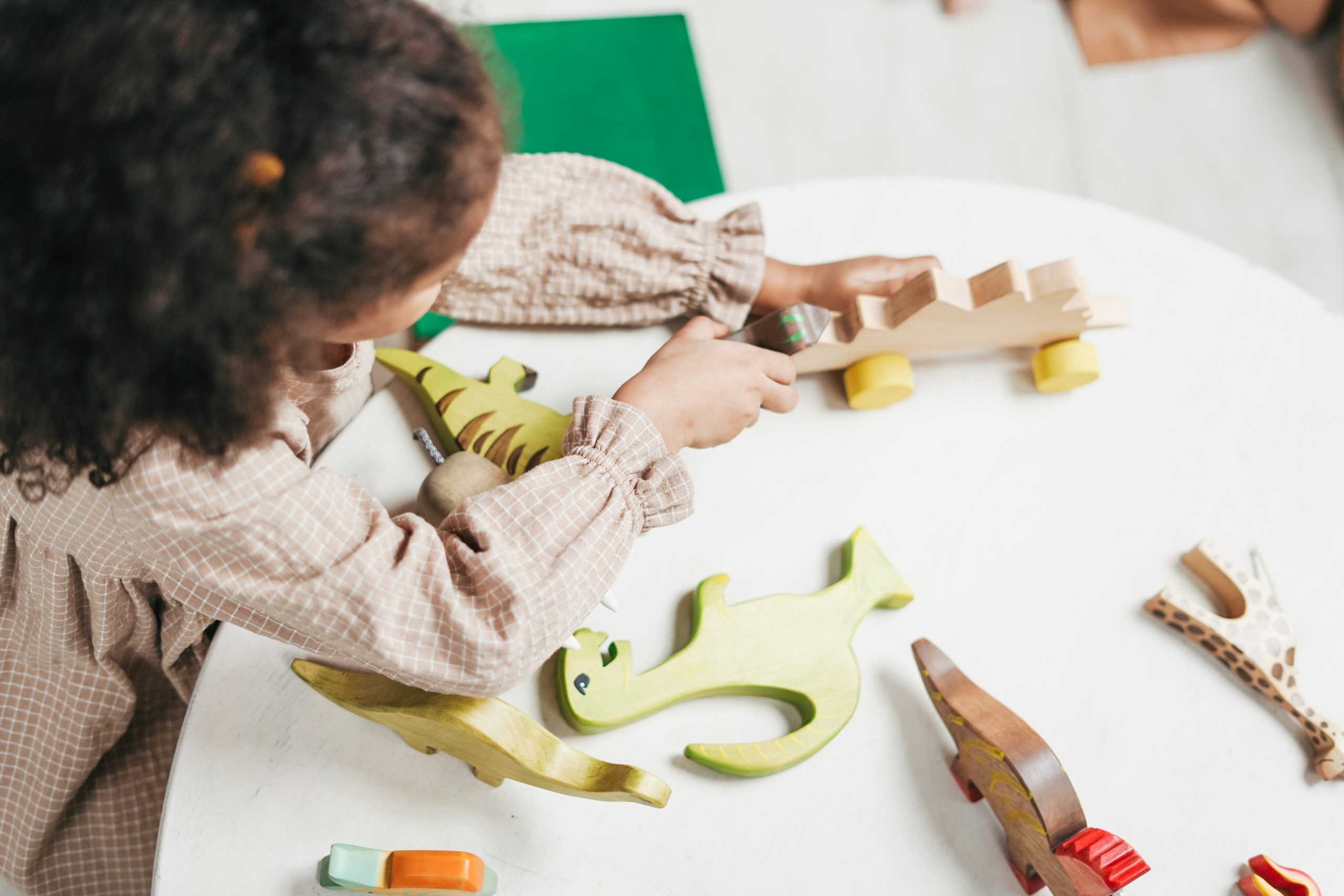 Canva - Overhead Photo of Young Girl Playing with Wooden Toys on White Table
