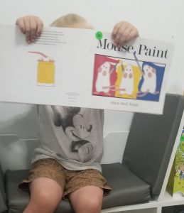 boy holding mouse paint book for color mixing activity 1