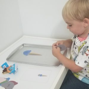boy sitting at desk with ice cream counting magnet board