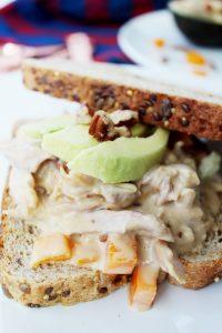 closeup chicken salad sandwich with avocado in back 1