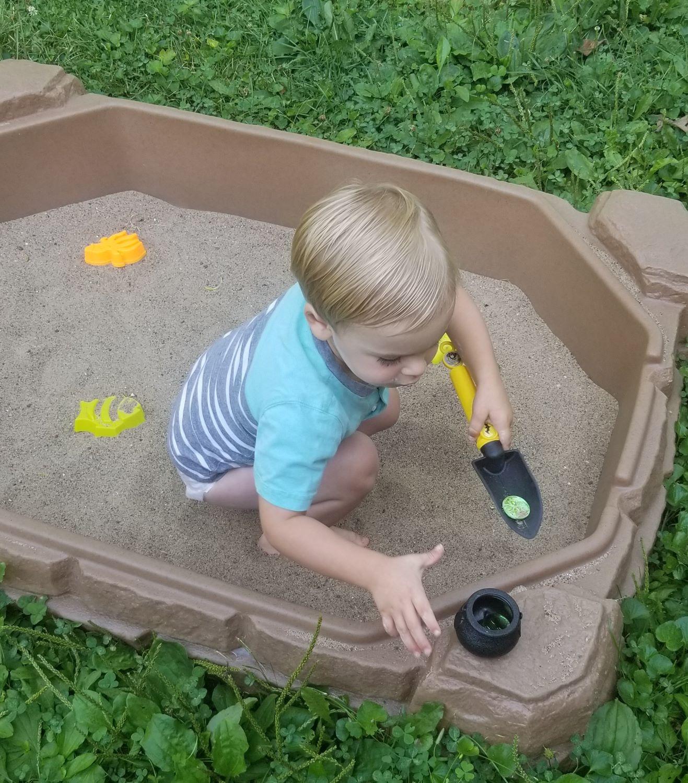 boy digging in sandbox coin hunt preschool homeschool