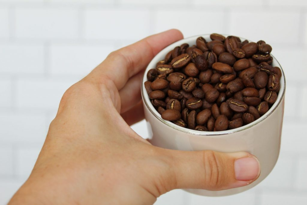 hand holding coffee cup beanshand holding coffee cup beans