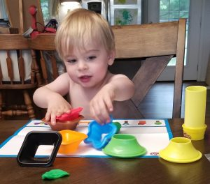 boy playing with play doh shapes 1