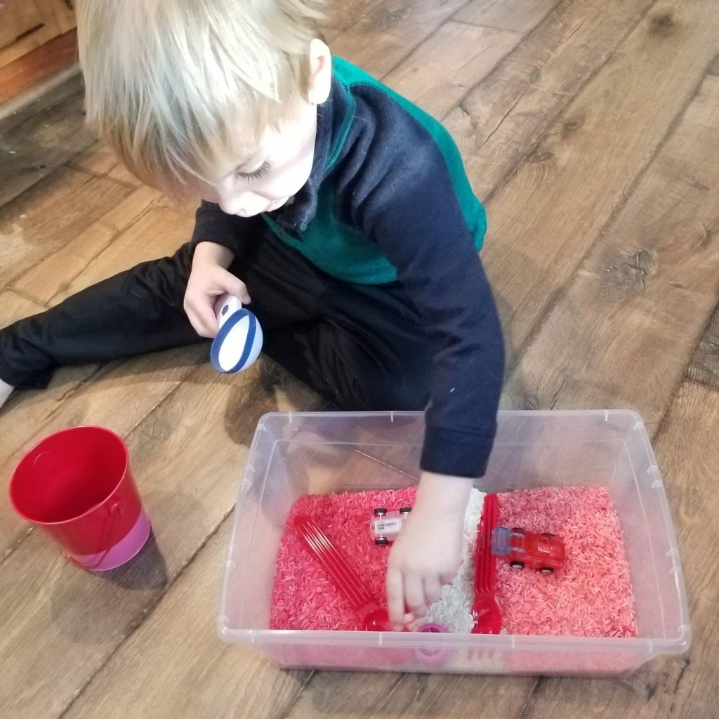 boy playing with valentine's day sensory rice bin
