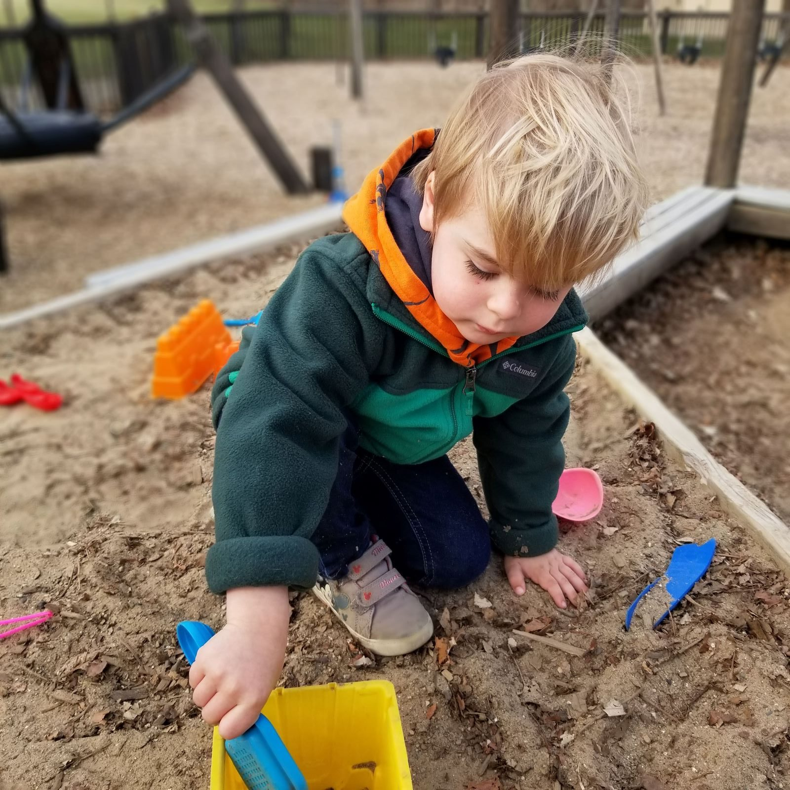 preschool boy playing in sandbox